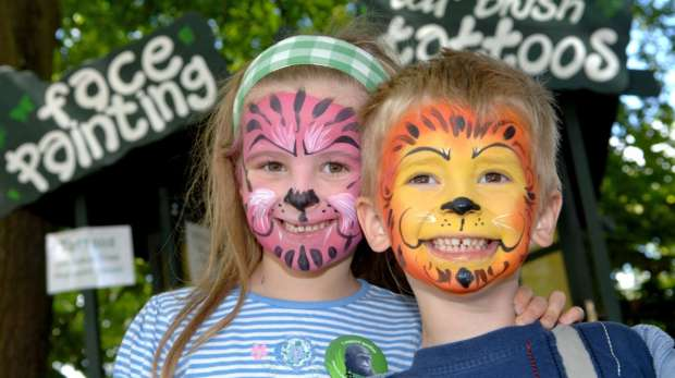 Two children with their faces painted at the zoo