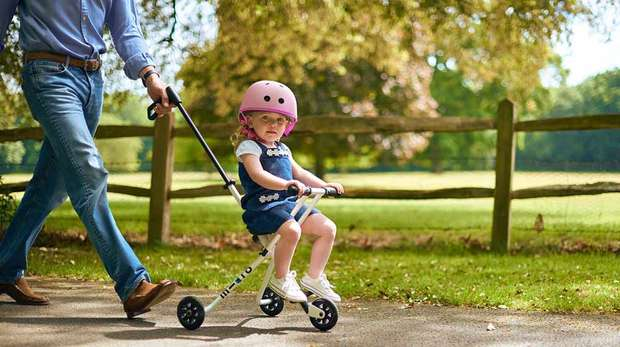 Little girl riding Micro Trike at Whipsnade Zoo pushed by dad in jeans