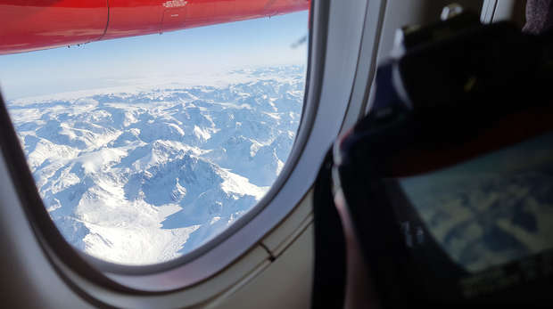A view of snowy mountain tops from the window of a plane