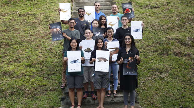 Picture of twelve people holding up posters of Asian EDGE species whilst standing on steps with a grassy backgruond